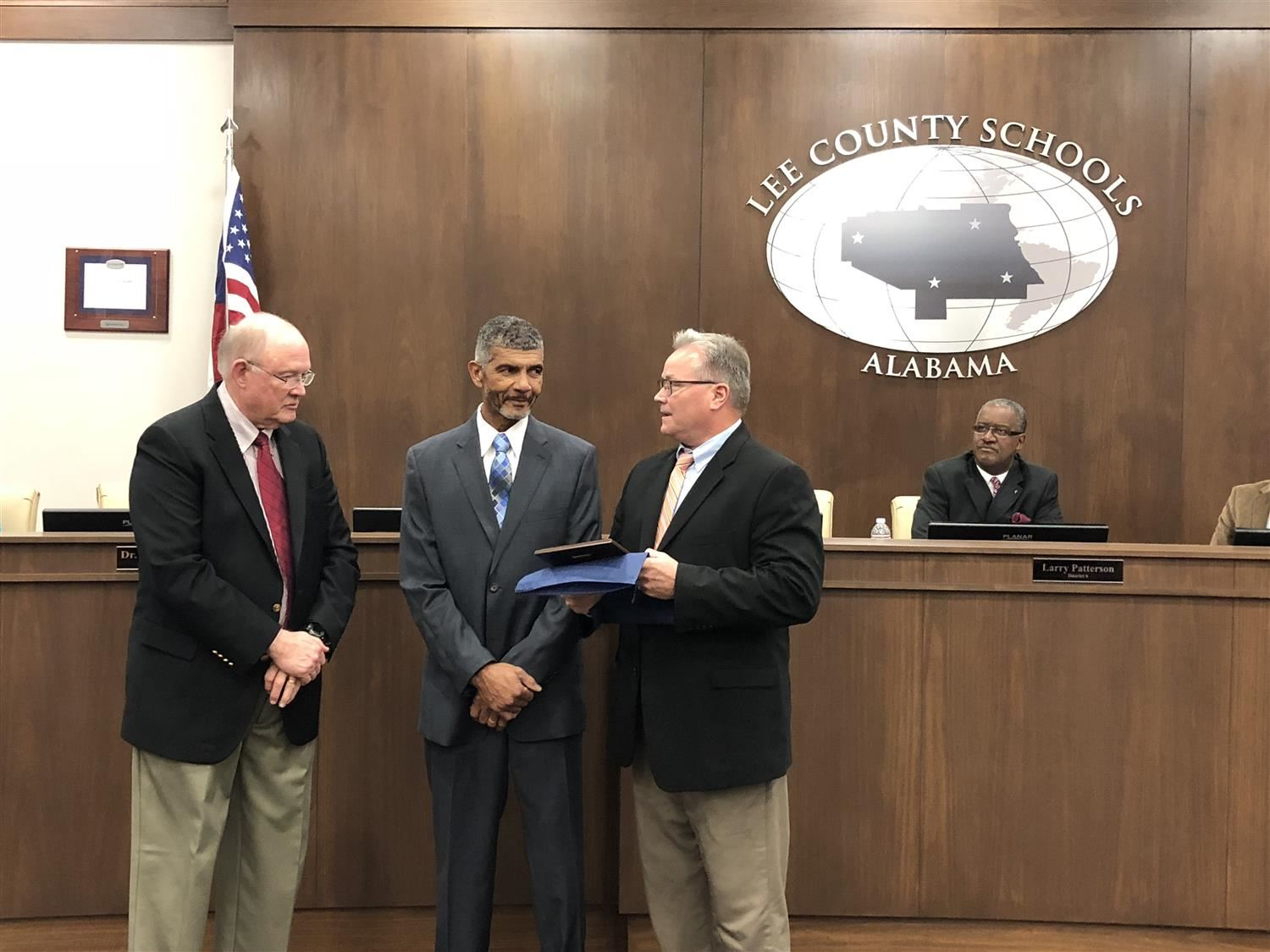 President of the Board, Mr. Larry Boswell, and Superintendent, Dr. Mac McCoy, present an award of recognition to Mr. Stringer