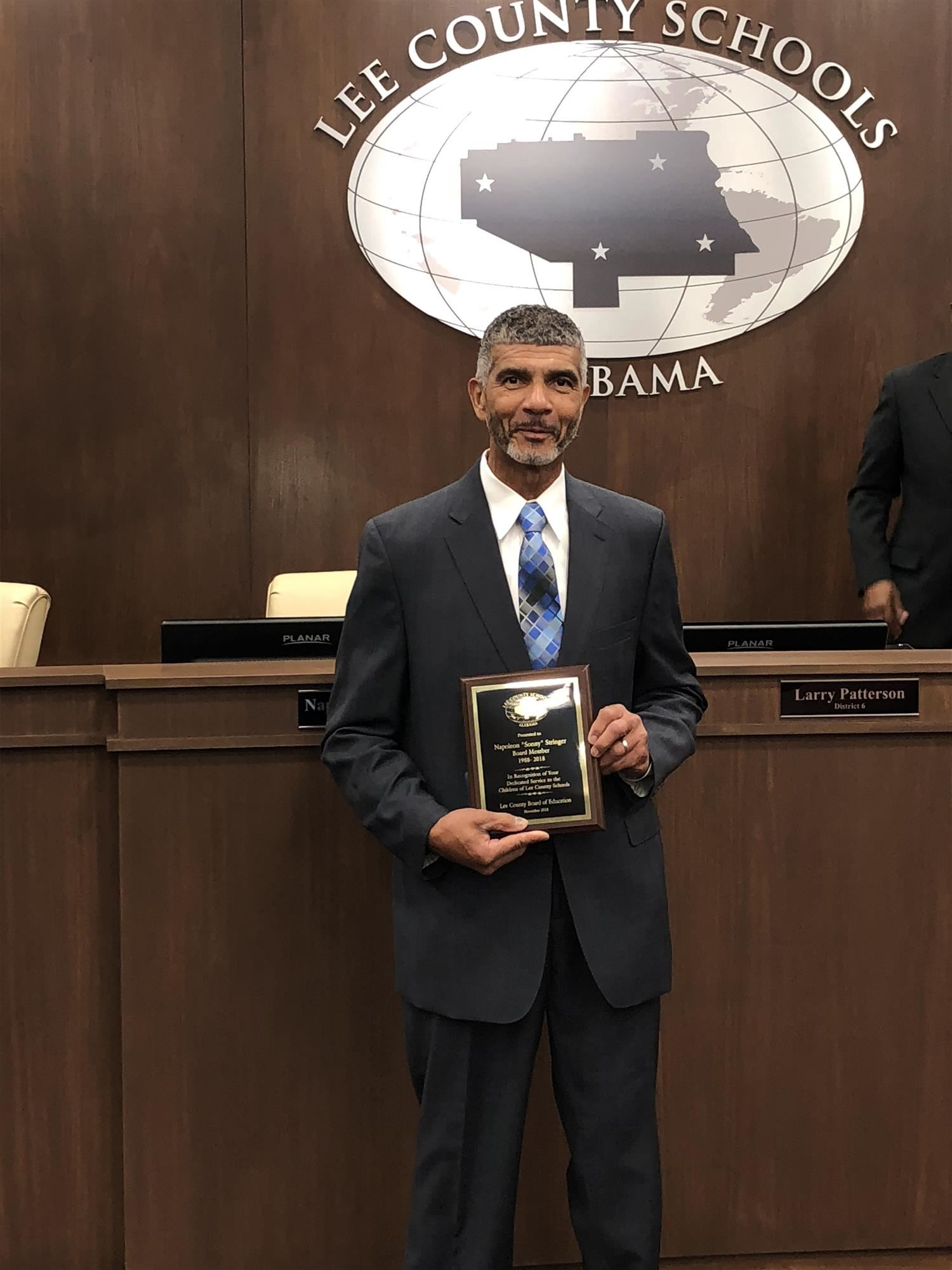 Outgoing Board Member Napoleon Stringer with plaque of recognition